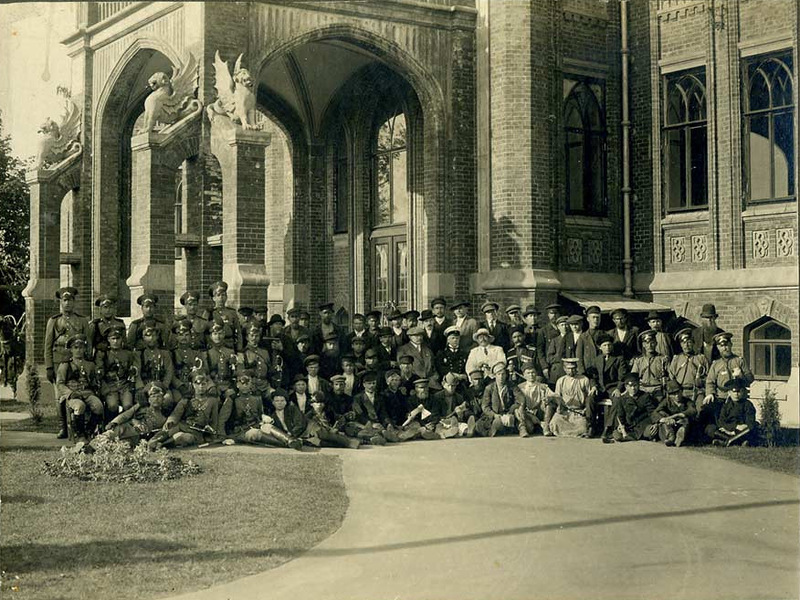 У подъезда особняка Т. Ф. Булычева. Во втором ряду в центре — губернский архитектор И.А. Чарушин (в форменном мундире и фуражке с белой тульей), рядом с ним, справа — Н. Г. Джмухадзе (в белом костюме и белой шляпе). Ориентировочно 1911 г.